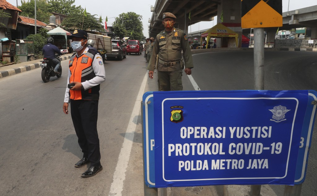 Officers stand guard at a police check point as the large-scale restriction is imposed to curb the spread of the coronavirus outbreak in Jakarta, Indo...