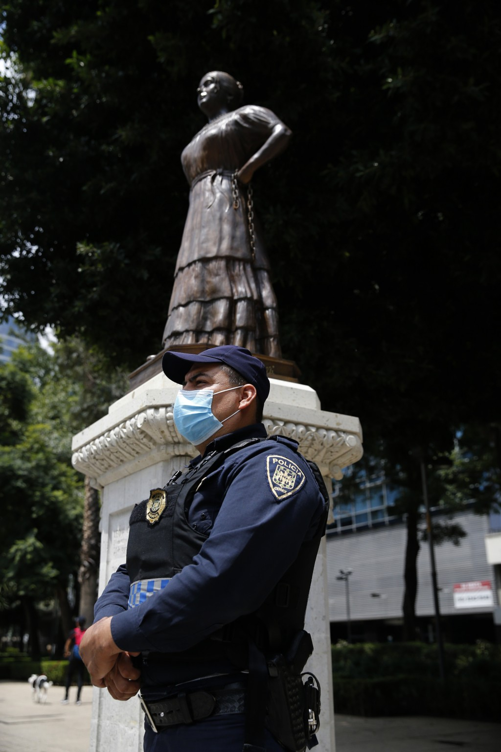 A police officer stands guard near a statue of independence heroine Leona Vicaria on Paseo de la Reforma in Mexico City, Sunday, September 13, 2020. M...