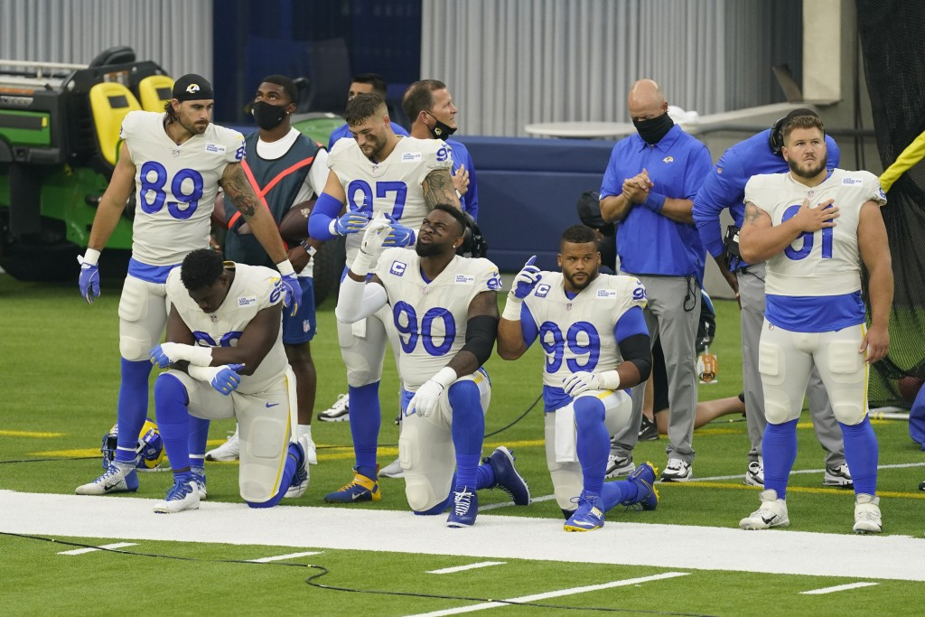 Members of the Los Angeles Rams stand and kneel during the national anthem before an NFL football game against the Dallas Cowboys Sunday, Sept. 13, 20...