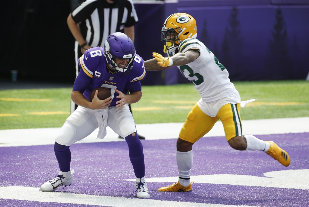 Green Bay Packers cornerback Jaire Alexander tackles Minnesota Vikings quarterback Kirk Cousins (8) in the end zone for a safety during the first half...