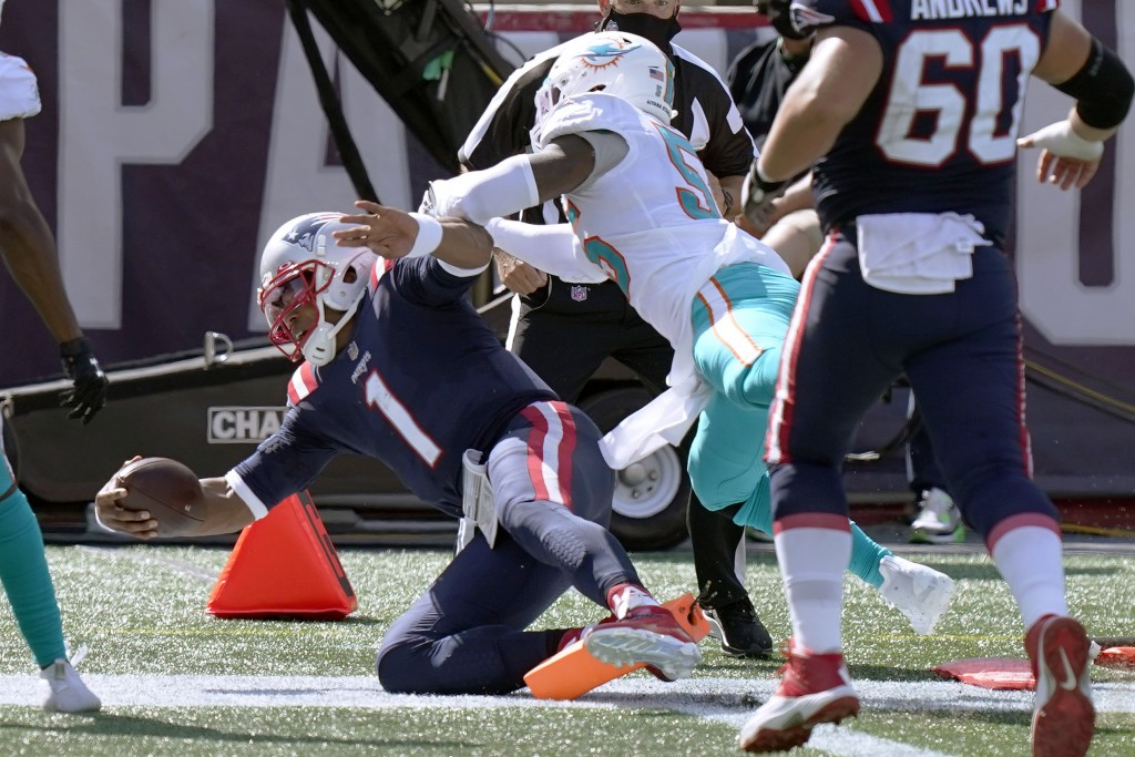 New England Patriots quarterback Cam Newton (1) scores his second rushing touchdown as Miami Dolphins linebacker Jerome Baker (55) chases in the secon...