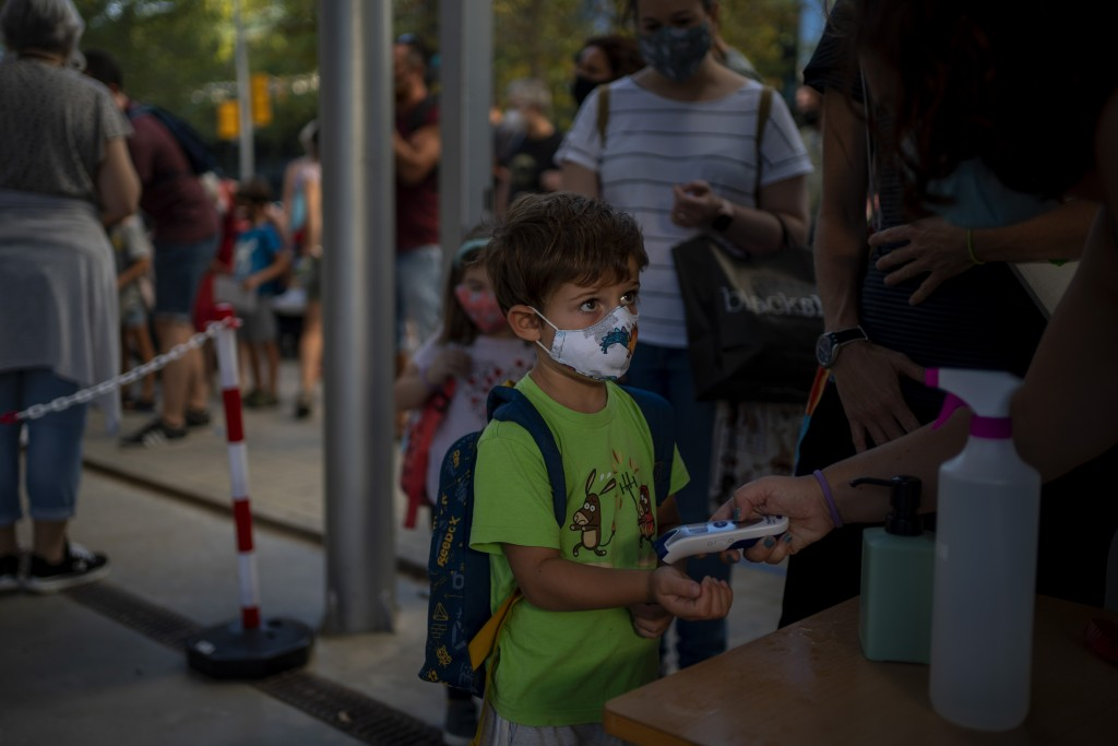 A student wearing a face mask to prevent the spread of coronavirus, has his temperature checked, prior to entering the school in Barcelona, Spain, Mon...