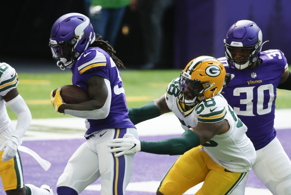 Minnesota Vikings running back Dalvin Cook scores on a 1-yard touchdown run ahead of Green Bay Packers outside linebacker Christian Kirksey (58) durin...