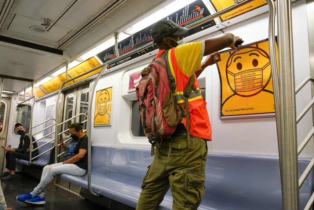 An MTA employee replaces posters reminding commuters to wear face masks in a subway car, Monday, Sept. 14, 2020, in the Brooklyn borough of New York. ...
