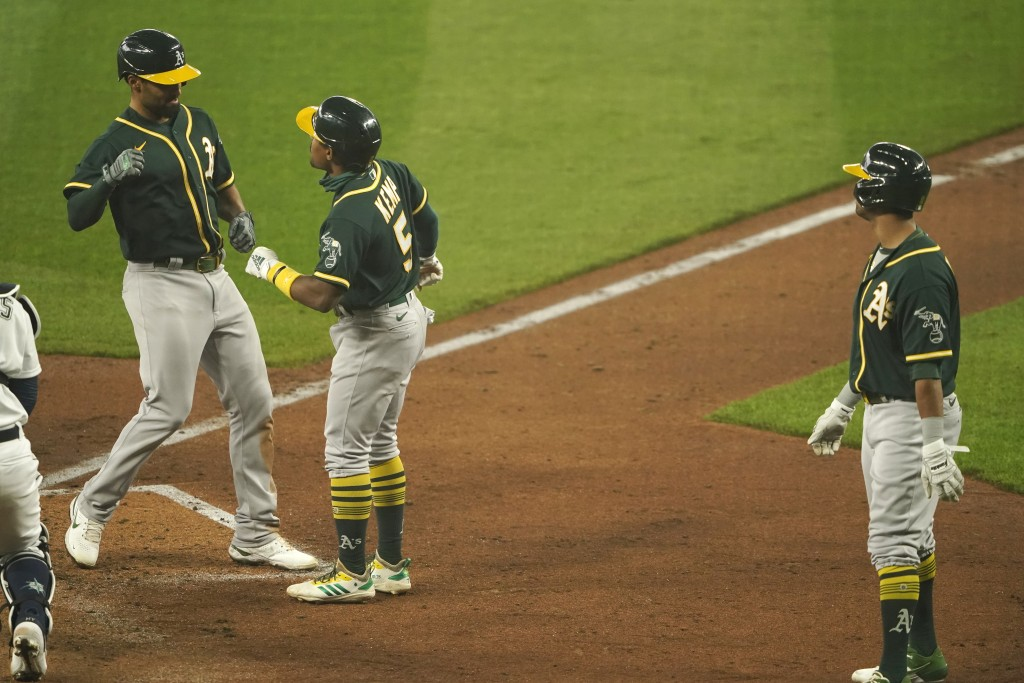 Oakland Athletics' Marcus Semien, left, is greeted by Tony Kemp after hitting a three-run home run to score Kemp and Khris Davis, right, during the fo...