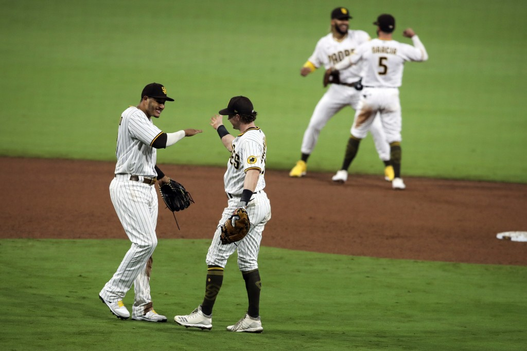 San Diego Padres third baseman Manny Machado, left, celebrates with Jake Cronenworth after beating the Los Angeles Dodgers in a baseball game, Monday,...