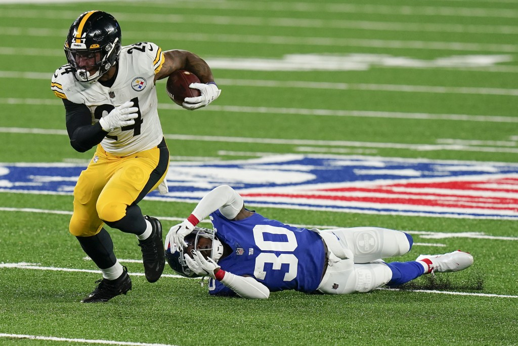Pittsburgh Steelers running back Benny Snell (24) avoids a tackle by New York Giants cornerback Darnay Holmes (30) during the first quarter of an NFL ...