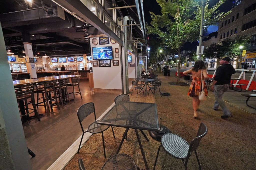 FILE - In this Sept, 9, 2020, file photo, a couple walk past Mike's Beer Bar, across the street from PNC Park, after a baseball game between the Chica...