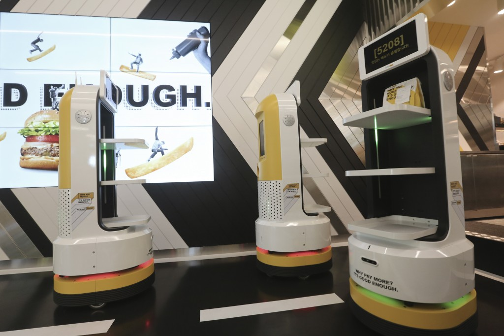 In this Sunday, Sept. 13, 2020, photo, a robot carries a takeout bag with food at No Brand Burger in Seoul, South Korea. From order to pick-up, custom...