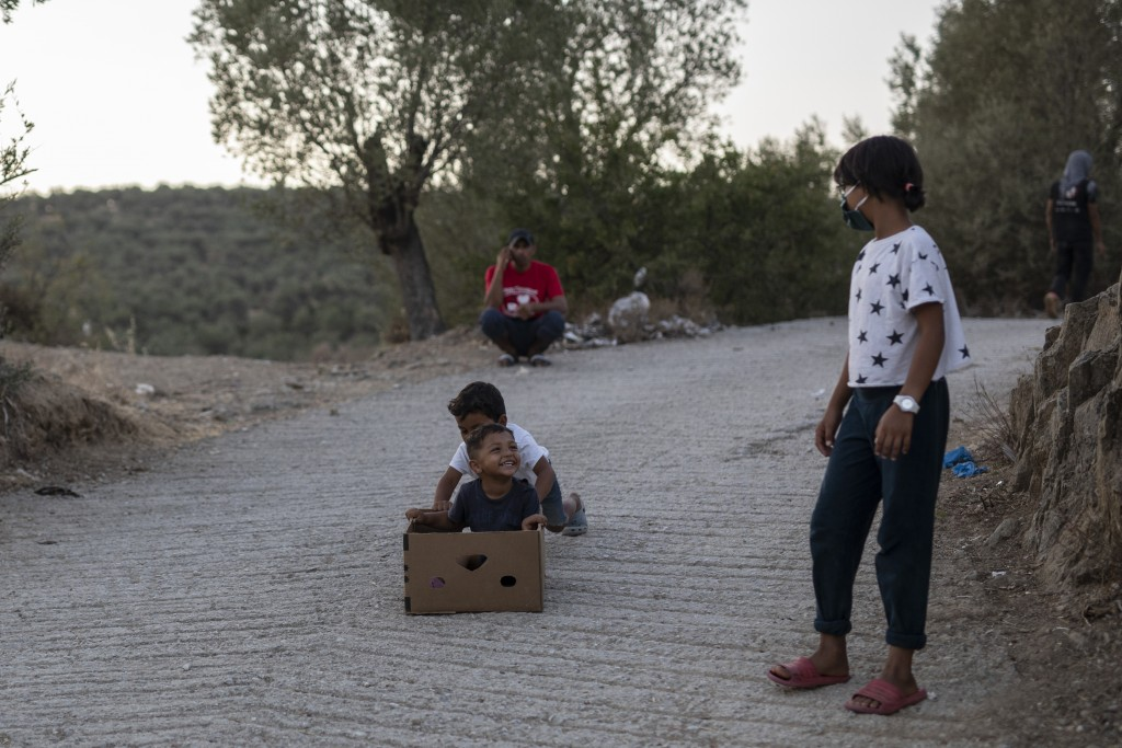 Children play near the burned Moria refugee camp, on the northeastern island of Lesbos, Greece, Monday, Sept. 14, 2020. Greece's prime minister demand...
