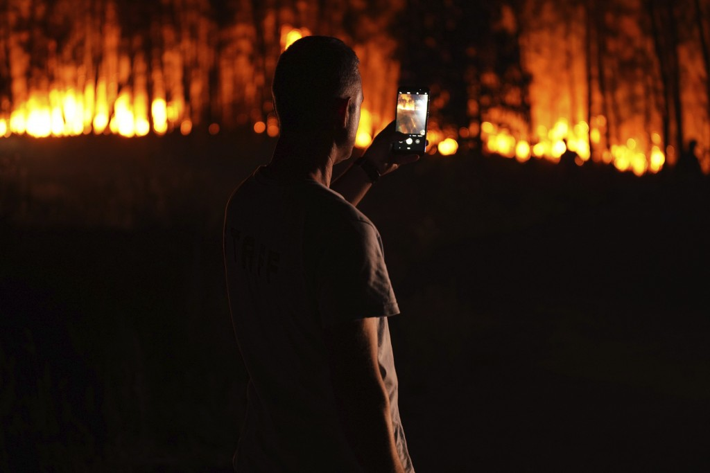 A man takes photos of a fire outside the village of Roqueiro, near Oleiros, Portugal, Monday, Sept. 14, 2020. Almost 1,000 firefighters are battling a...