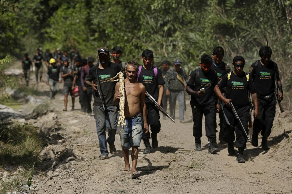 Altemir Freitas Mota carries a tool used in cutting down trees as he leads Tenetehara Indigenous men from the Ka'Azar, or Forest Owners, to his group'...