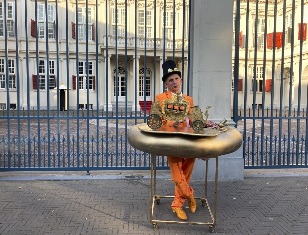 """Resplendent in orange suit, tie and shoes and a black hat with gold bow and protected by a homemade """"corona bumper"""" decorated with a model carriage, J..."""