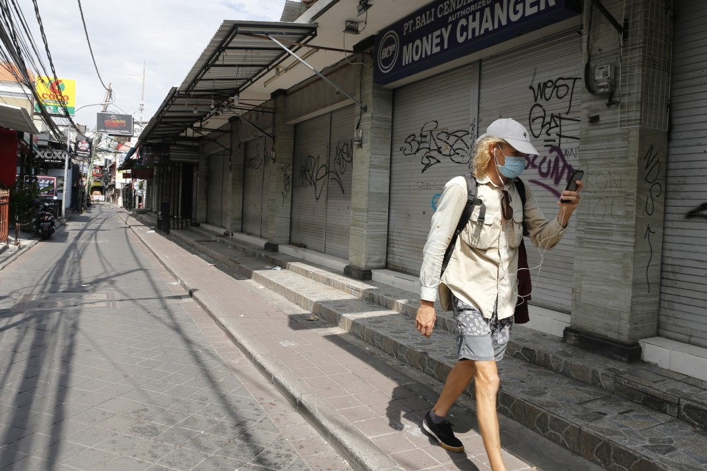 FILE - In this April 14, 2020, file photo, a foreign tourist walks along an empty road lined with closed shops in Bali, Indonesia. The Asian Developme...