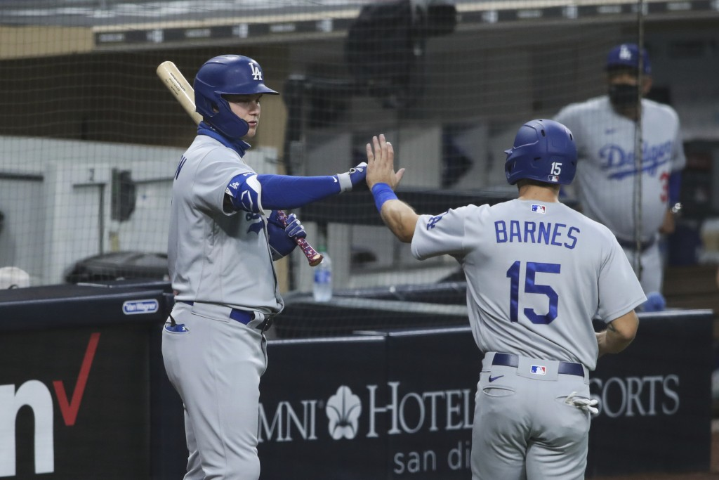 Los Angeles Dodgers' Joc Pederson high-fives Austin Barnes after he scored on a fielder's choice against the San Diego Padres in the third inning of a...
