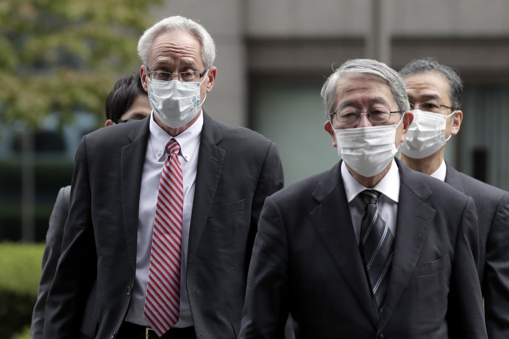 Former Nissan Motor Co. executive Greg Kelly, left, arrives for the first trial hearing at the Tokyo District Court in Tokyo Tuesday, Sept. 15, 2020. ...