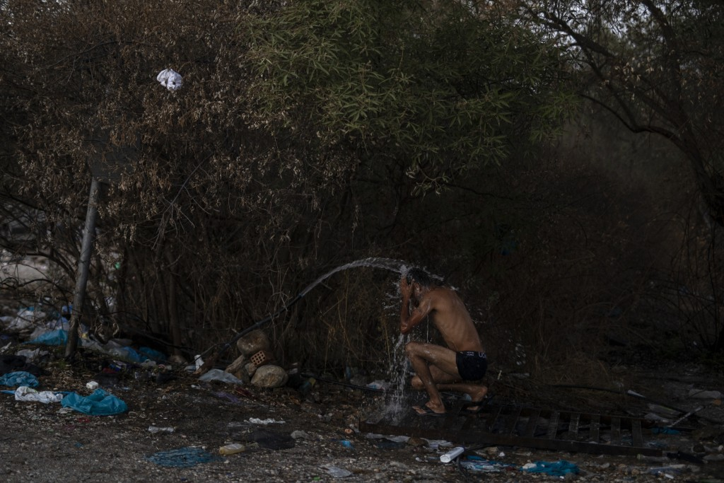 A migrant uses water from a plastic pipe to wash himself outside the burned Moria refugee camp, on the northeastern island of Lesbos, Greece, Monday, ...