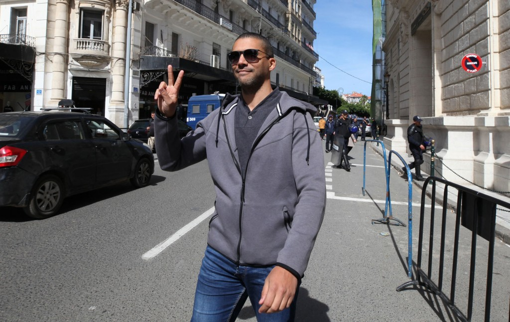 FILE - In this March 10, 2020 file photo, Algerian journalist Khaled Drareni flashes the V sign as he leaves the courthouse in Algiers. An Algerian co...