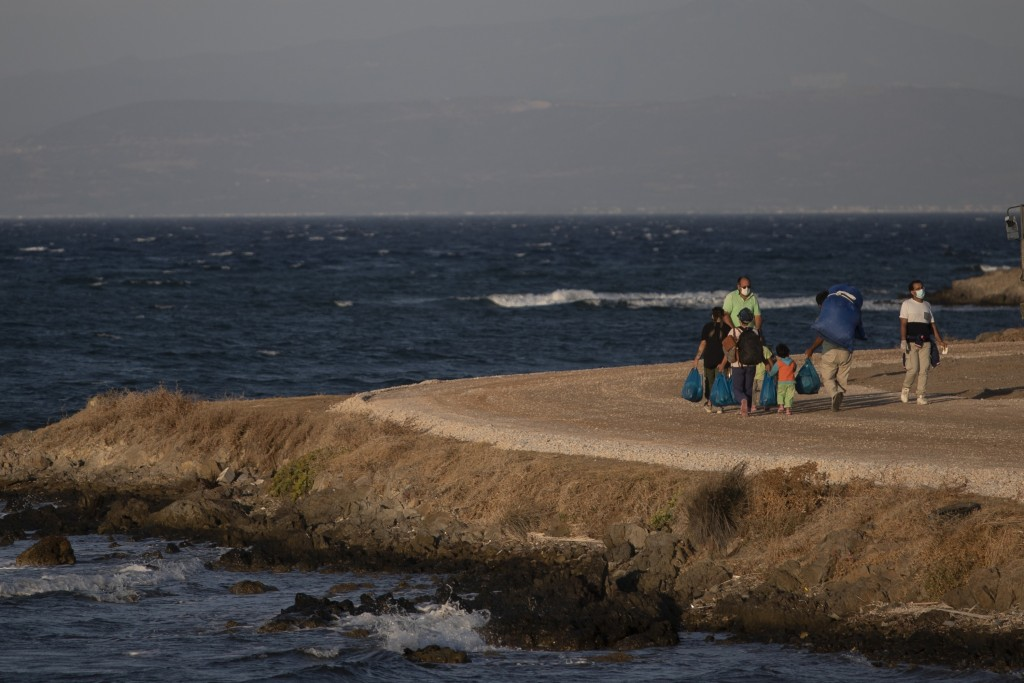 Migrants with their belongings walk near the new temporary refugee camp in Karatepe near Mytilene town, on the northeastern island of Lesbos, Greece, ...