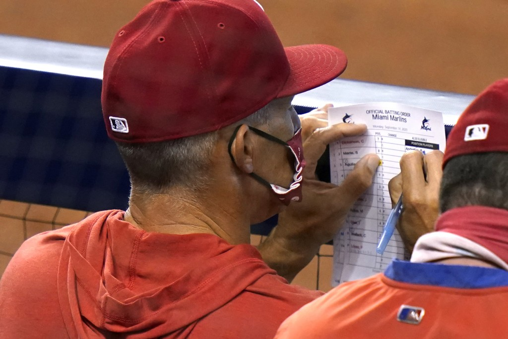 Philadelphia Phillies manager Joe Girardi looks at the lineup during the fourth inning of a baseball game against the Miami Marlins, Monday, Sept. 14,...