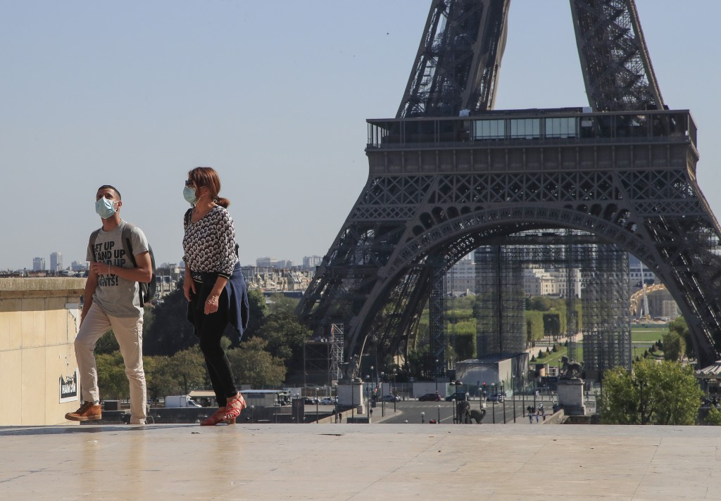 People wearing protective face masks as precaution against the conoravirus walk at Tocadero plaza near Eiffel Tower in Paris, Monday, Sept. 14, 2020. ...