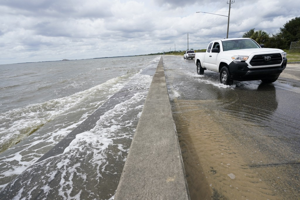 Waters from the Guld of Mexico poor onto a local road, Monday, Sept. 14, 2020, in Waveland, Miss. Hurricane Sally, one of a record-tying five storms c...
