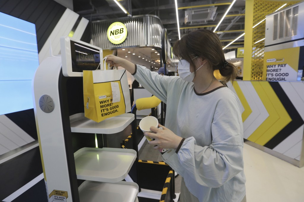 In this Sunday, Sept. 13, 2020, photo, a customer picks up a takeaway bag with food from a robot at No Brand Burger in Seoul, South Korea. These robot...