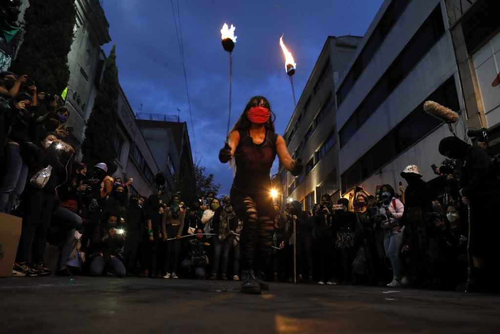 A woman performs with fire as feminist and crime victims who have been occupying the offices of the governmental Human Rights Commission celebrate an ...