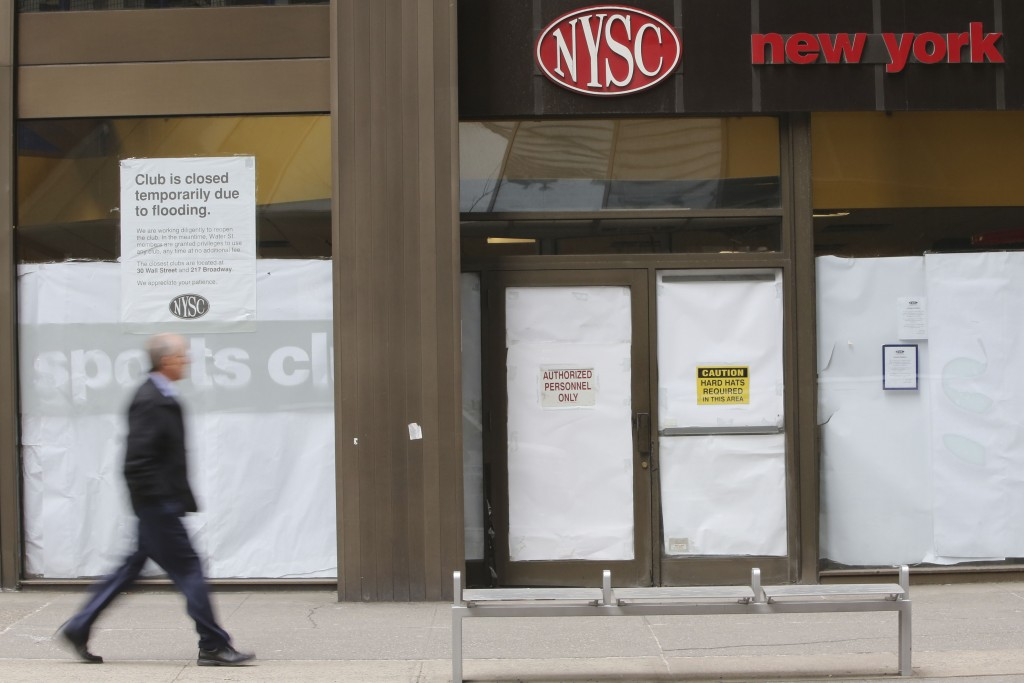 FILE - In this Feb. 7, 2013 photo, a man walks past a shuttered New York Sports Club on Water St. in New York. Town Sports International Holdings Inc....