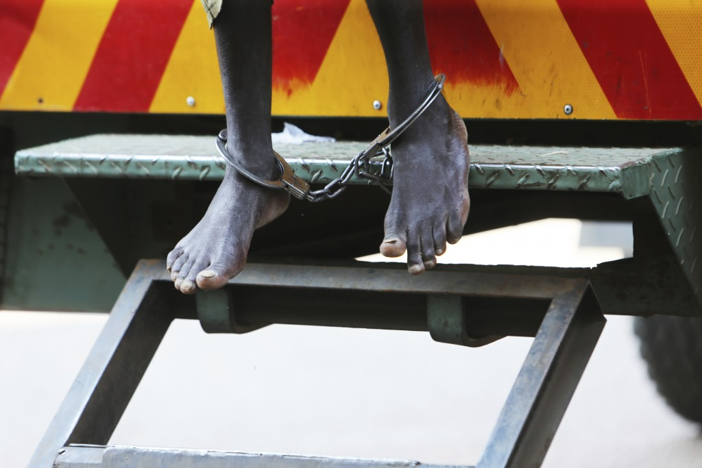 A man arrested for protesting over human rights abuses makes a court appearance in leg irons at the magistrates courts in Harare, Monday, Sept. 14, 20...
