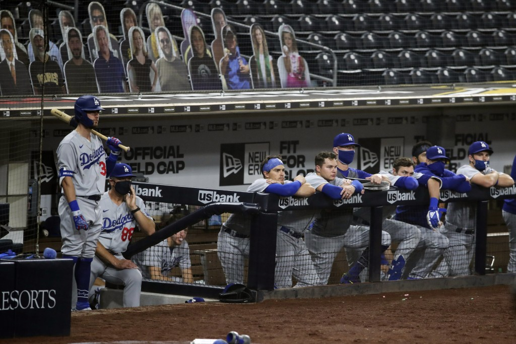 Members of the Los Angeles Dodgers watch from the top step of the dugout while trailing the San Diego Padres in the ninth inning of a baseball game, M...