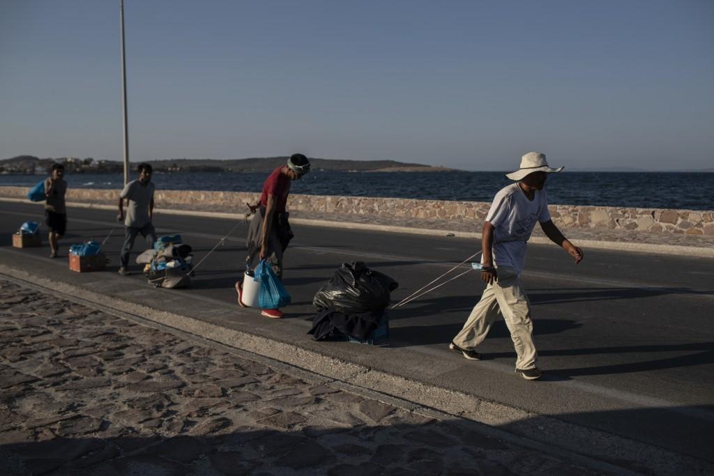 Migrants pull their belongings as they walk on a road near Mytilene town, on the northeastern island of Lesbos, Greece, Monday, Sept. 14, 2020. Greece...