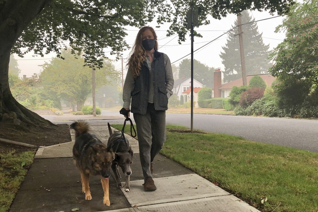 Zoe Flanagan walks her dogs amid dense smoke from wildfires in Portland, Ore., on Monday, Sept. 14, 2020. Wildfires across the U.S. West have created ...