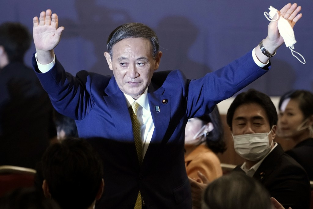 FILE- In this Sept. 14, 2020, file photo, Japanese Chief Cabinet Secretary Yoshihide Suga acknowledges as he is elected as new head of Japan's ruling ...