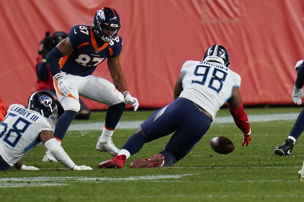 Tennessee Titans defensive tackle Jeffery Simmons (98) recovers a fumble as Denver Broncos tight end Noah Fant (87) looks on during the first half of ...