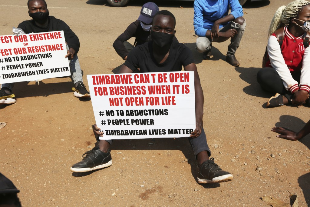 A student and human rights activist holds a banner during a peaceful protest in Harare, Monday, Sept. 14, 2020. Human rights defenders say it appears ...