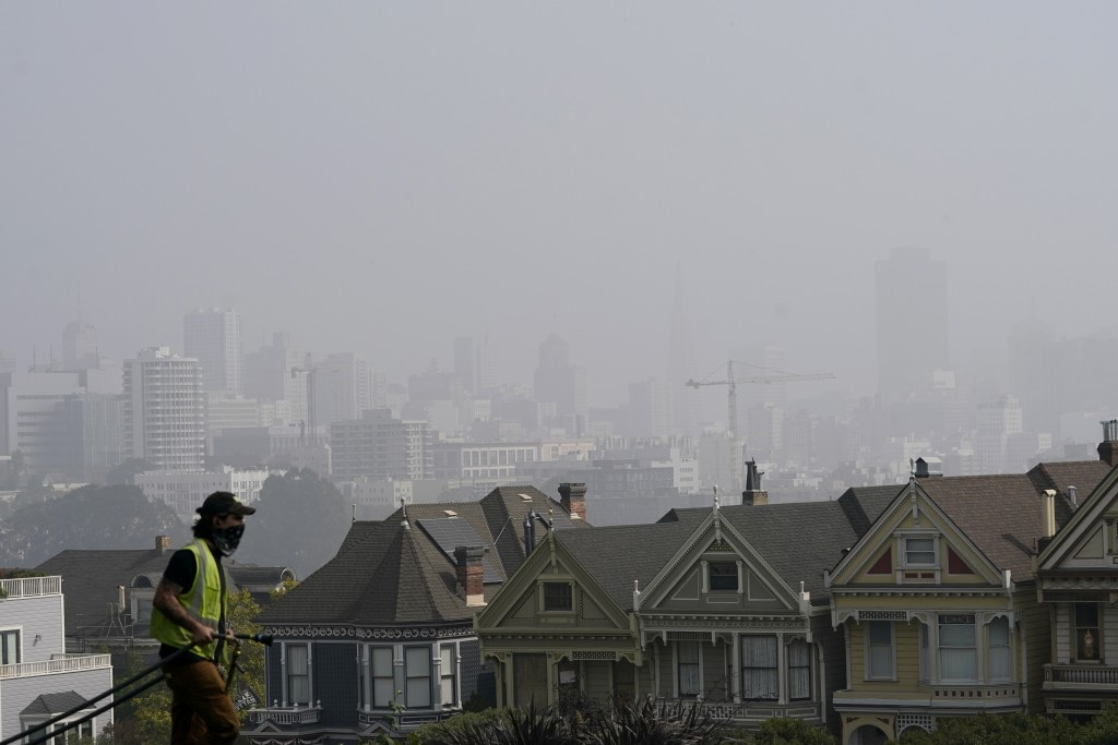 "A worker cleans grass at Alamo Square Park as smoke from wildfires and fog obscures the skyline above the ""Painted Ladies,"" a row of historical Victor..."