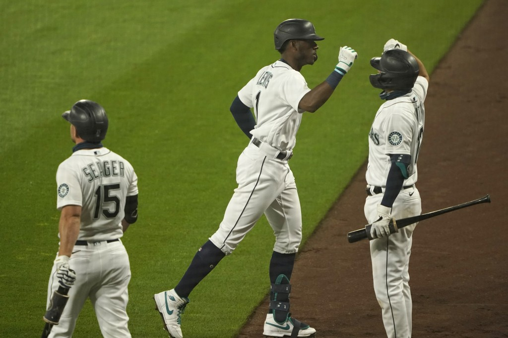 Seattle Mariners' Kyle Lewis, center, is greeted by Evan White, right, as Kyle Seager (15) looks on after Lewis hit a two-run home run against the Oak...