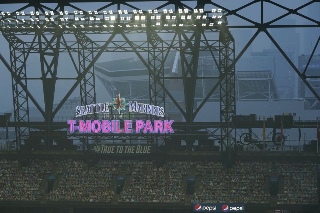 Smoke from wildfires fills the air at T-Mobile Park as photos of fans are displayed in the left field bleachers and CenturyLink Field is visible behin...