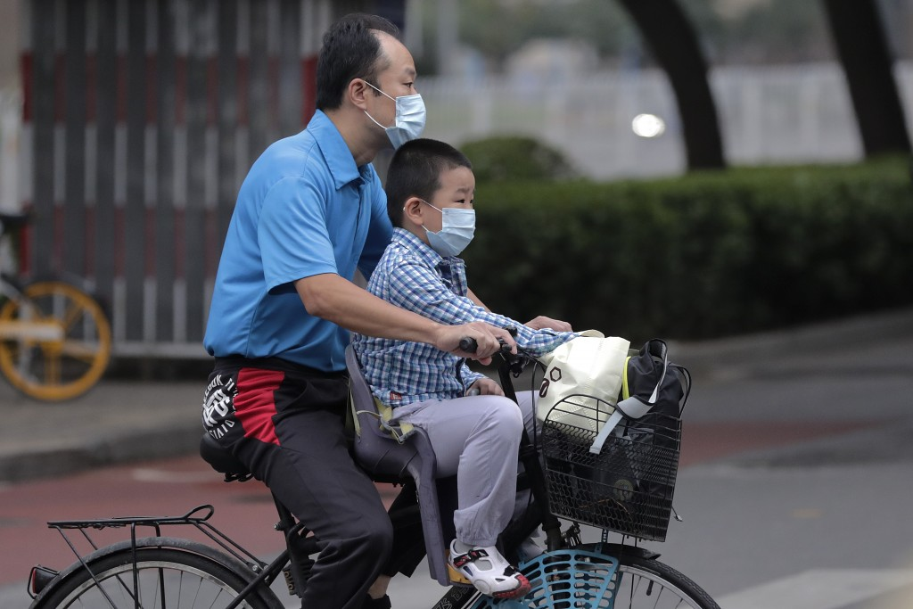 A man and a child wearing face masks to help curb the spread of the coronavirus ride on a bicycle past a street in Beijing, Tuesday, Sept. 15, 2020. E...