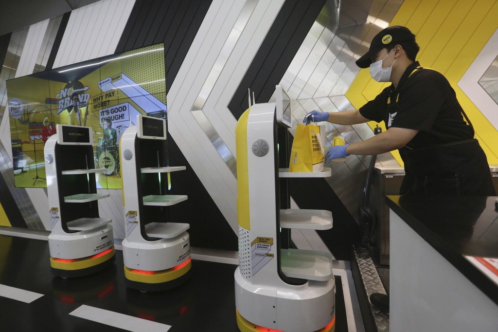 In this Sunday, Sept. 13, 2020 photo, an employee places a takeout bag with food at a robot at No Brand Burger in Seoul, South Korea. These robotic se...