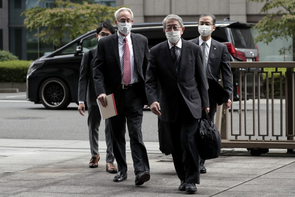 Former Nissan Motor Co. executive Greg Kelly, left in foreground, arrives for the first trial hearing at the Tokyo District Court in Tokyo Tuesday, Se...