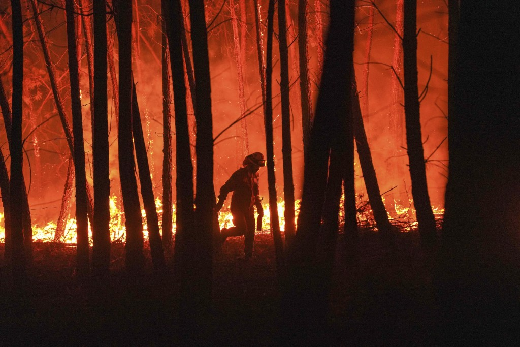 A firefighter is silhouetted against a fire burning outside the village of Roqueiro, near Oleiros, Portugal, Monday, Sept. 14, 2020. Almost 1,000 fire...