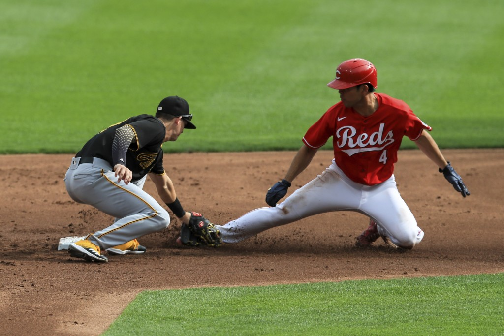 Pittsburgh Pirates' Kevin Newman, left, tags out Cincinnati Reds' Shogo Akiyama, right, who was attempting to steal second base in the first inning du...