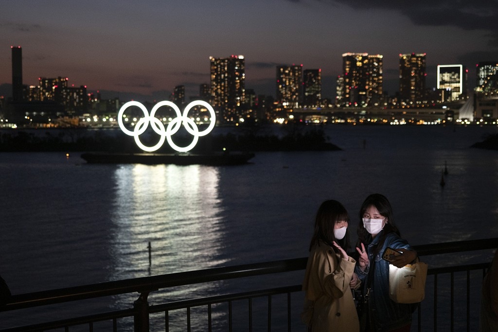 In this March 12, 2020, file photo, two women take a selfie with the Olympic rings in the background in the Odaiba section of Tokyo. The CEO of the To...