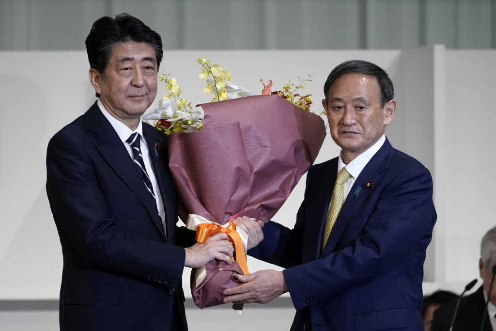 FILE - In this Sept. 14, 2020, file photo, Japan's Prime Minister Shinzo Abe, left, receives flowers from Chief Cabinet Secretary Yoshihide Suga after...
