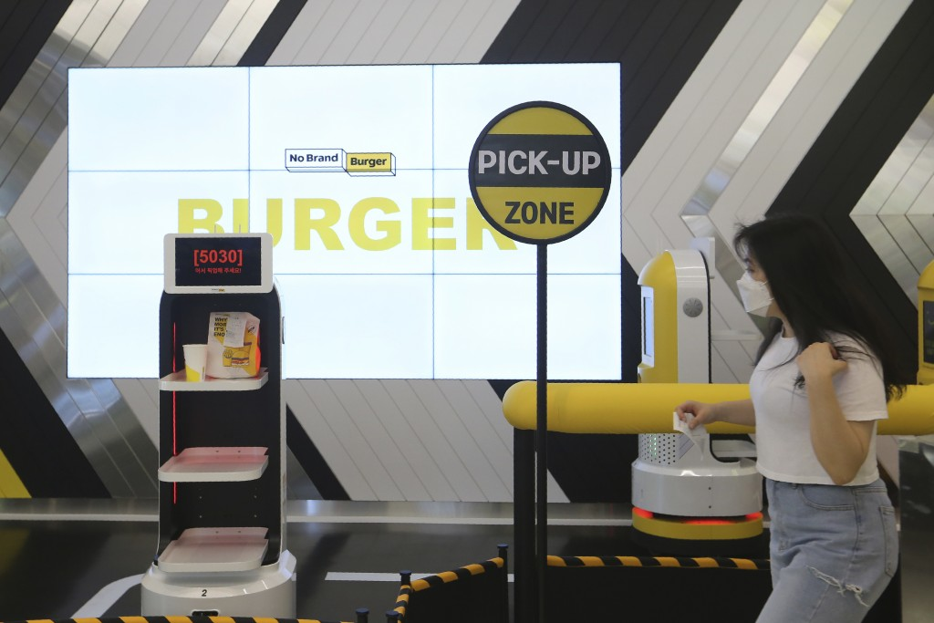 In this Sunday, Sept. 13, 2020, photo, a customer moves to pick up her takeout bag with food from a robot at No Brand Burger in Seoul, South Korea. Th...
