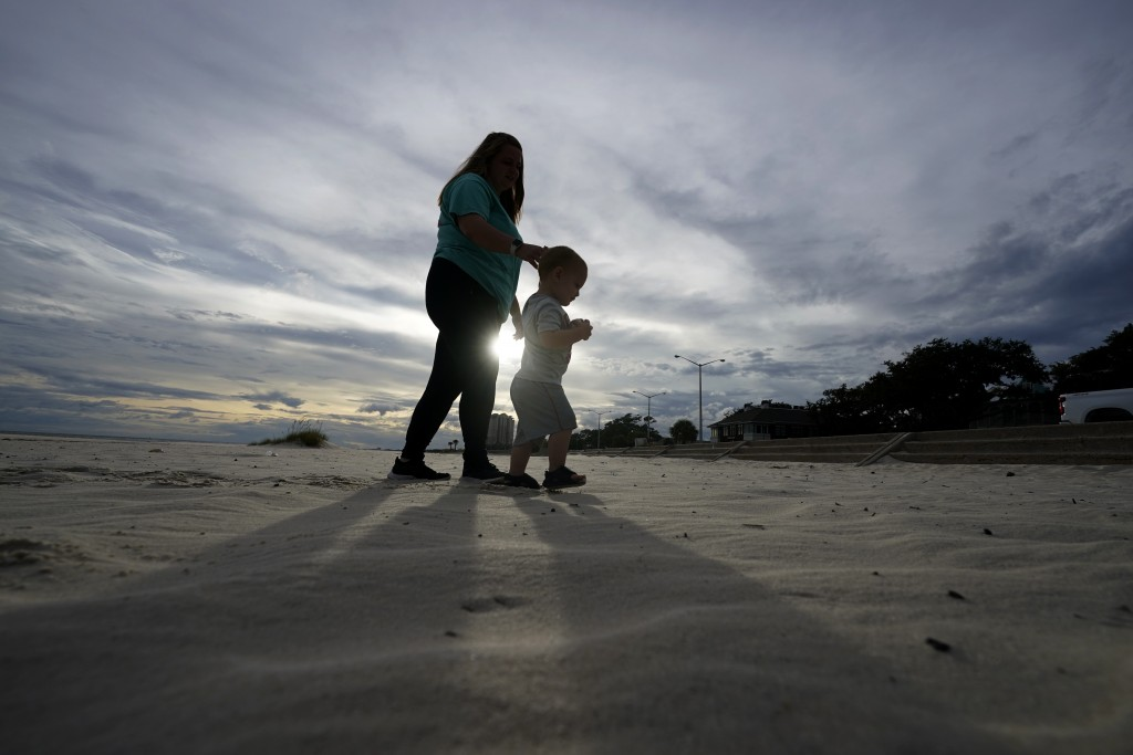 Nikita Pero of Gulfport, Miss., walks with her son Vinny Pero, 2, on the beach along the Gulf of Mexico in Biloxi, Miss., Monday, Sept. 14, 2020. Hurr...