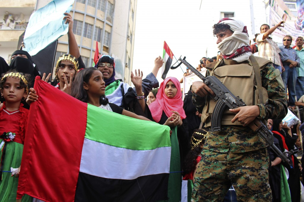 FILE - In this Sept. 5, 2019 file photo, a girl holds the flag of the United Arab Emirates during a rally of supporters of southern separatists to sho...