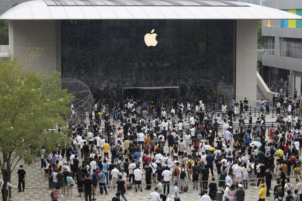 FILE - In this July 17, 2020, file photo, Apple fans cheer as the doors to a new flagship store are opened at Sanlitun in Beijing. The Asian Developme...